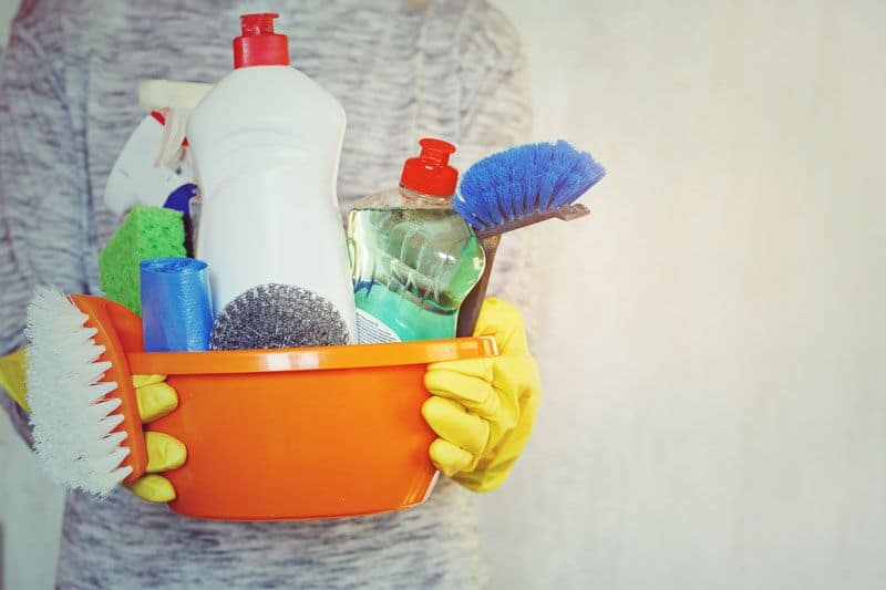 close up of person holding cleaning supplies