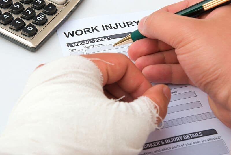 man in cast filling out a workers compensation claim form