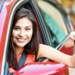 teen driver leaning out of her car