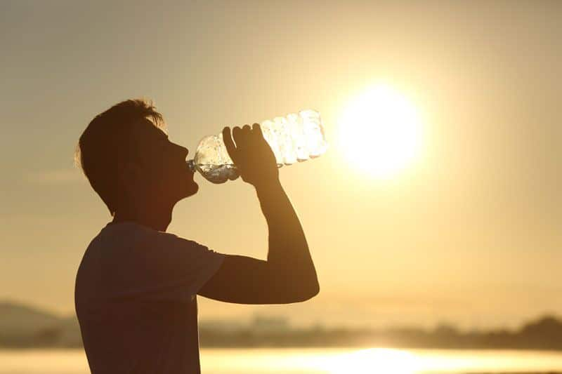 person drinking water in the sun