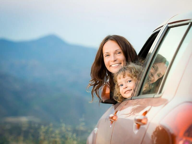 mom and child sticking their head out of car window