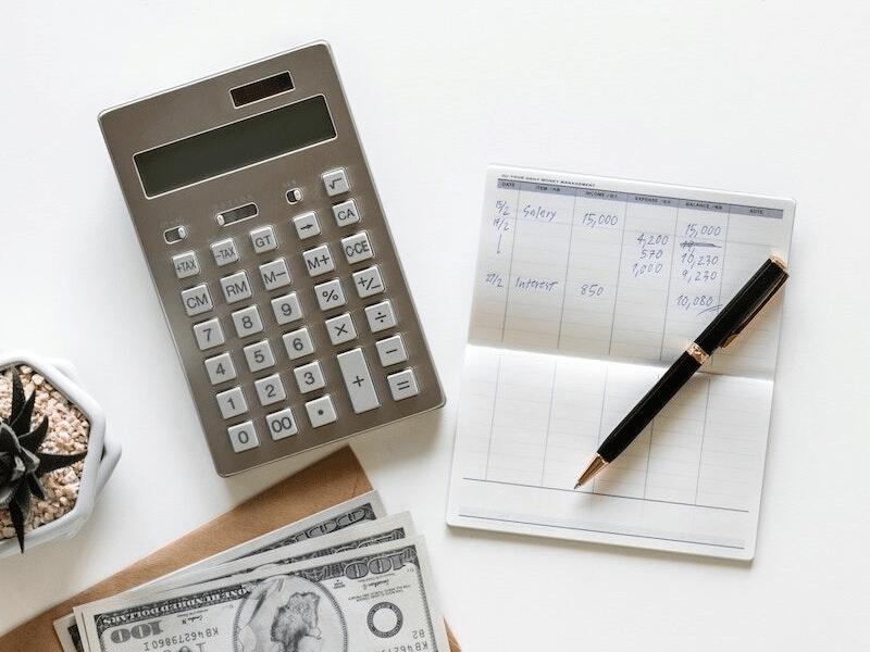 calculator, checkbook, and cash