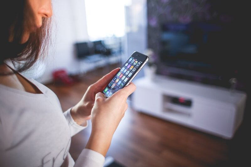 woman using smartphone in front of smart TV